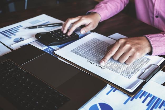Mannetje dat computerlaptop en calculator gebruikt om effectenbeurs te analyseren