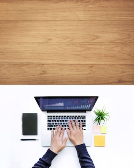 Mannetje dat computerlaptop op de witte houten achtergrond van de bureautafel met behulp van.