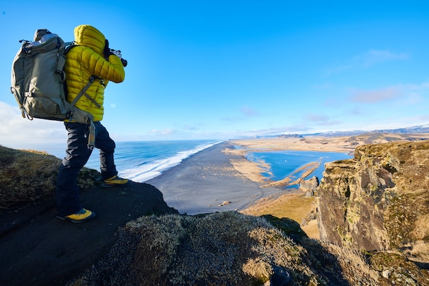 Mannetje dat een geel jasje draagt dat op een rots staat terwijl hij een foto neemt van het prachtige landschap