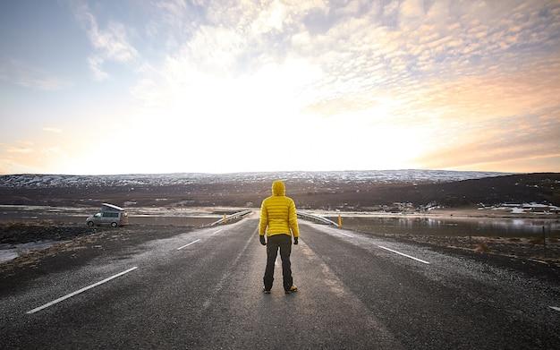 Mannetje dat een geel jasje draagt terwijl hij midden op een lege weg staat en in de verte kijkt