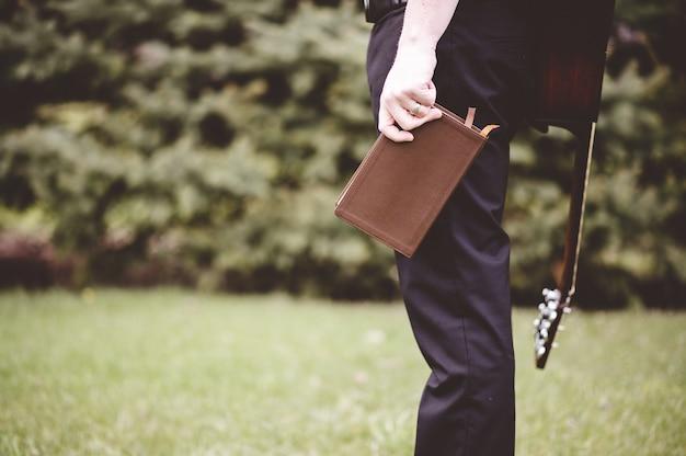 Mannetje dat een notitieboekje houdt en een gitaar op zijn rug in een park draagt