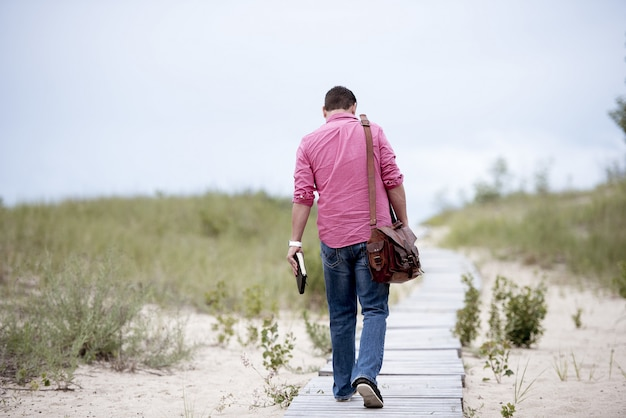Mannetje dat een notitieboekje houdt lopend op een houten weg in het midden van zandige oppervlakte
