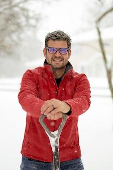 Mannetje dat een rood de winterjasje met zijn handen op een sneeuwschop draagt