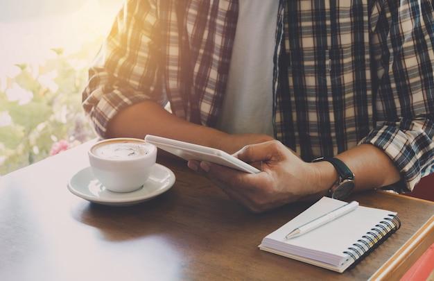 Mannetje dat een slimme telefoon met koffiekop op houten lijst gebruikt.