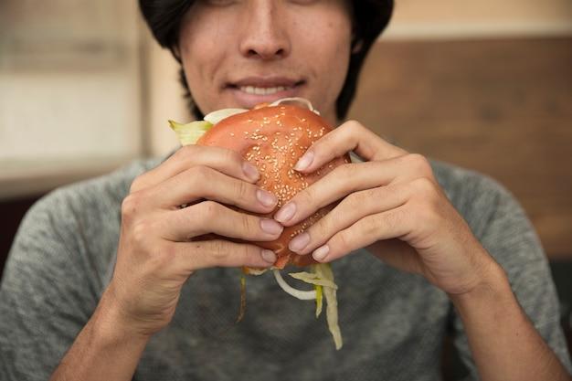Mannetje dat hamburger in koffie eet