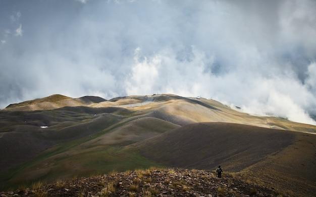 Mannetje dat op een berg met een bewolkte hemel loopt