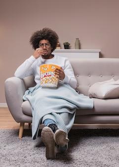 Mannetje dat popcorn op laag eet