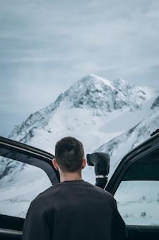 Mannetje dat zich naast zijn 4x4 auto bevindt en mooie sneeuwbergen in de alpen bekijkt