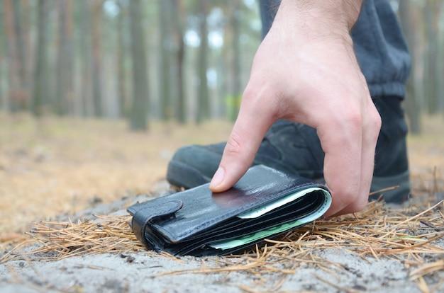 Mannetje die omhoog verloren portefeuille van een grond in de houten weg van de de herfstspar met de hand plukken. het concept van het vinden van een waardevol ding en veel geluk