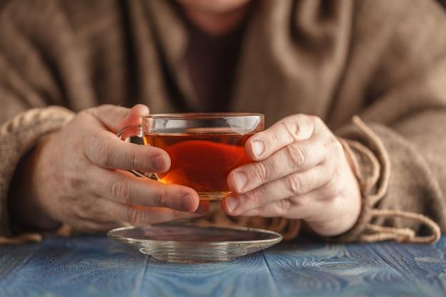 Mannetje drinkt hete thee in koude dag