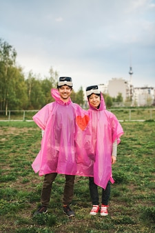Mannetje en een vrouw staan in het veld in een gedeelde roze plastic regenjas en hebben vr-headsets afgenomen