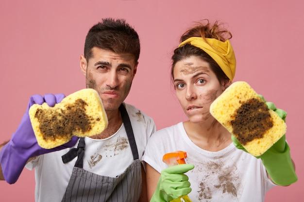 Mannetje en vrouwtje in vrijetijdskleding met vuile gezichten die vuile sponzen demonstreren