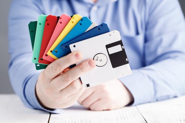 Mannetje houdt diskette in handen, retro opslag