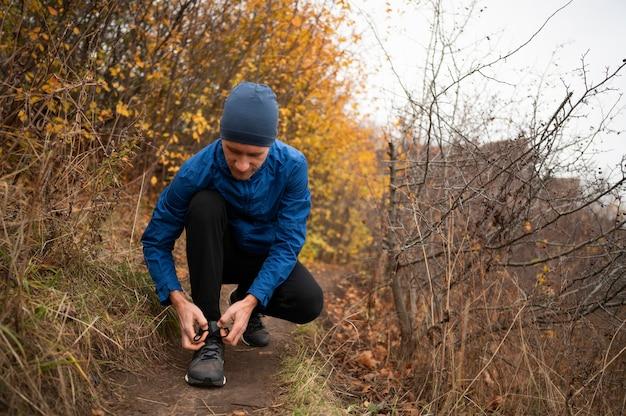 Mannetje in bos dat zijn schoenveters knoopt