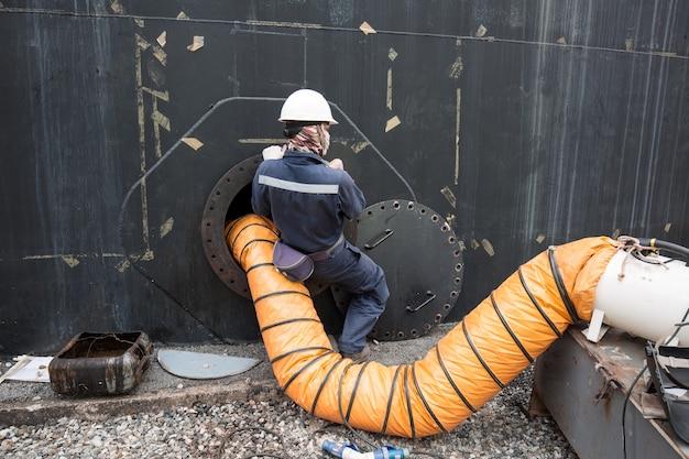 Mannetje in de zwarte brandstoftank oliegebied besloten ruimte veiligheidsventilator frisse lucht