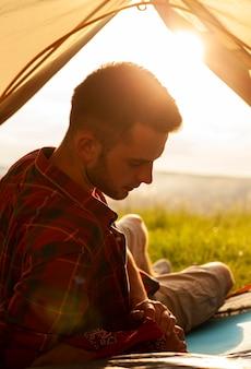Mannetje in het kamperen tent bij zonsondergang