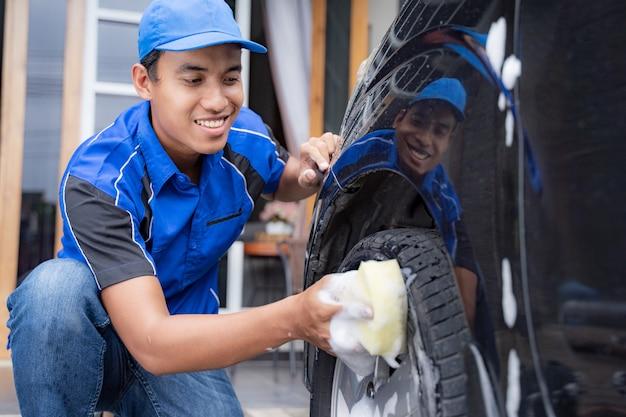 Mannetje in uniform het schoonmaken van de auto van zijn klant