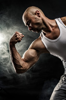 Mannetje in wit mouwloos onderhemd met sterke spieren op de zwarte achtergrond