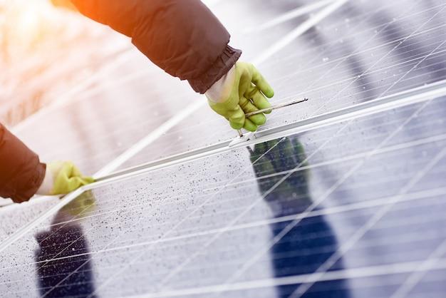 Mannetje installeert zonne-batterijen met behulp van gereedschap bij besneeuwd weer