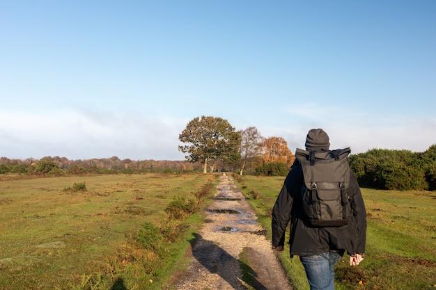 Mannetje met een rugzak die door een weg in een veld loopt