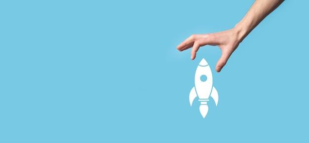Mannetje met raketpictogram dat opstijgt, lanceren op blauw oppervlak.