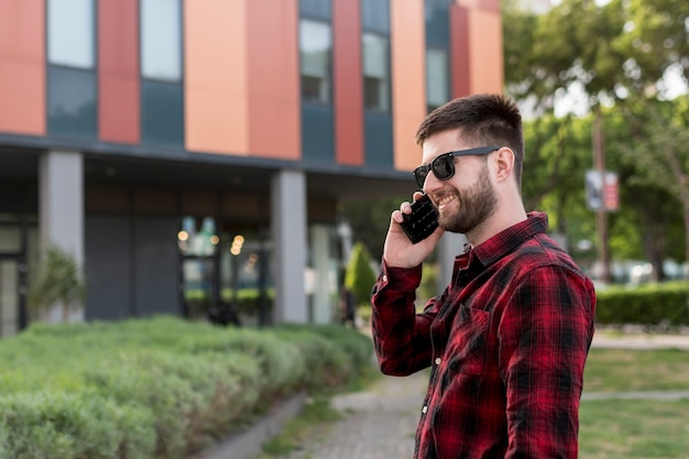 Mannetje met zonnebril die op smartphone spreken