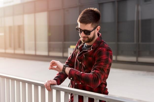 Mannetje met zonnebril die tijd controleert