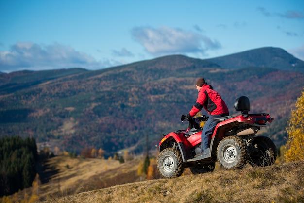 Mannetje op een atv die onderaan de heuvelige weg op een achtergrond van bergen, bos en blauwe hemel berijdt