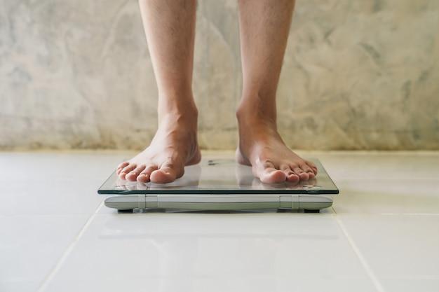Mannetje op gewichtsschaal op vloer, dieetconcept.