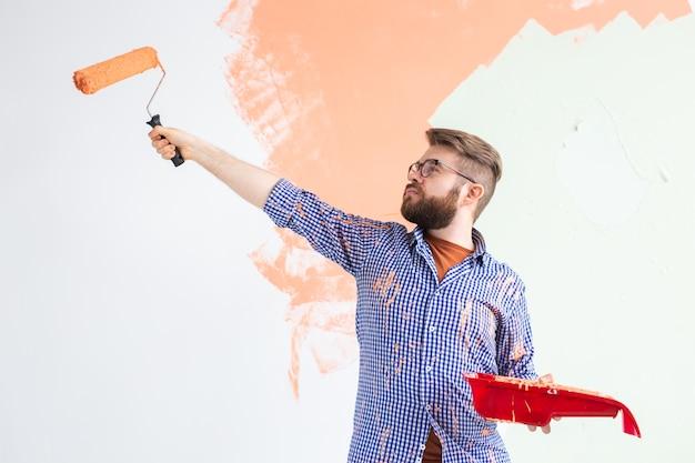 Mannetje schilderen van de muur met verfroller. portret van een grappige kerel die muur in haar nieuwe appartement schildert