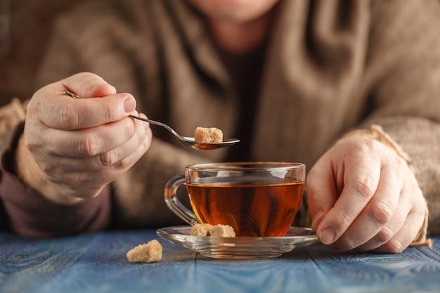 Mannetje voegt suiker toe in hete thee