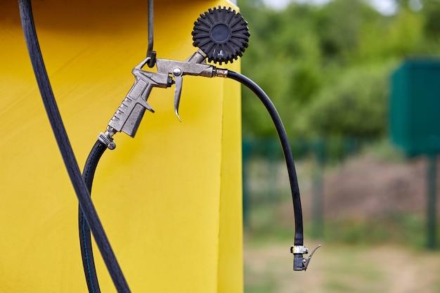 Manometer en pistool van compressoreenheid voor het oppompen van banden bij benzinestations