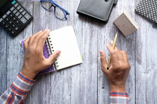 Mans hand een pager van een dagboek draaien en de kalenderdatum analyseren
