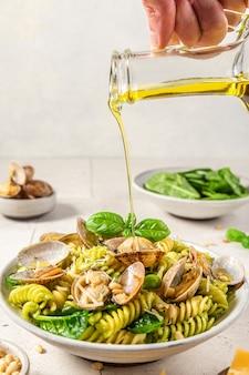 Mans hand gieten olijfolie in pasta met zeevruchten met vongole kokkels, spinazie, parmezaanse kaas, pijnboompitten en basilicum