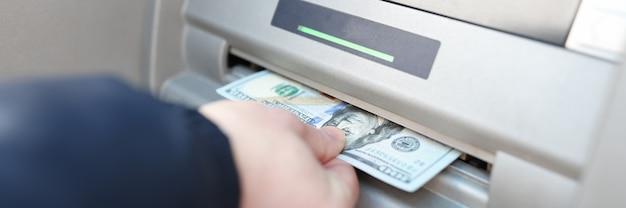Mans hand haalt bankbiljetten uit een klantenserviceconcept van een atm-bank Premium Foto