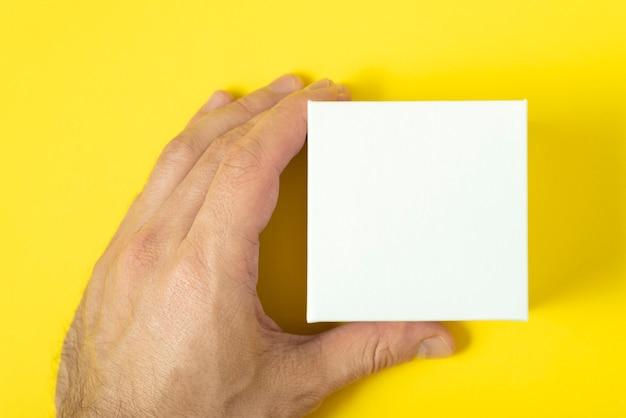 Mans hand houdt kleine witte doos op gele achtergrond.