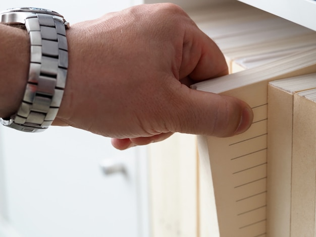 Mans hand in horloge haalt papier uit stapelarchief. optimalisatieproces acquisitiepakketten. drukt effectenformulieren binnen deze seriesheets af aanvraagformulieren op kantoor. sheet verwerkingsmethode