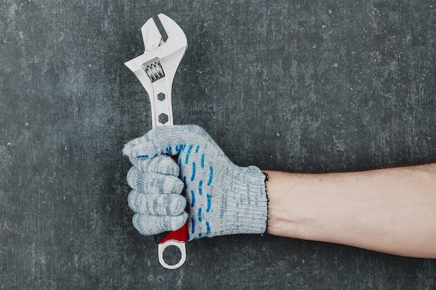 Mans hand met een verstelbare moersleutel