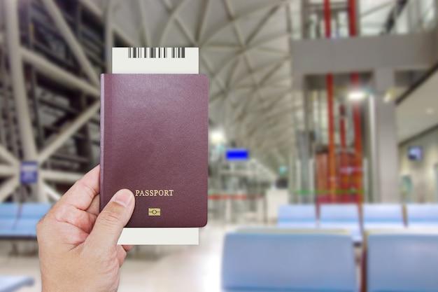 Mans hand met internationaal paspoort terwijl u aan de voorkant van de balie wacht om in te checken