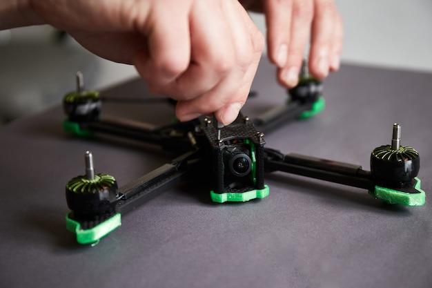 Mans handen assembleren een drone met behulp van gereedschappen die snelle race-quadcopter voorbereiden op de vlucht