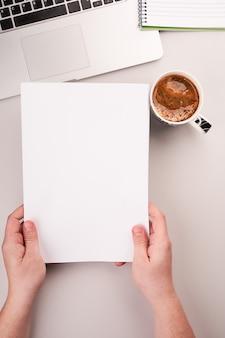 Mans handen met blanco papier op het bureau met computer en koffie
