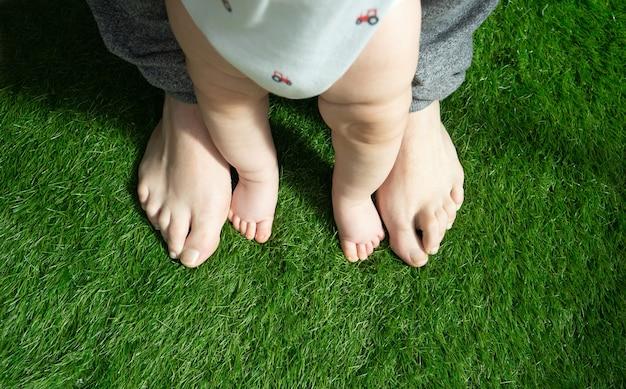 Mans voeten naast babys voeten op kunstgras eerste stappen ouderschap concept