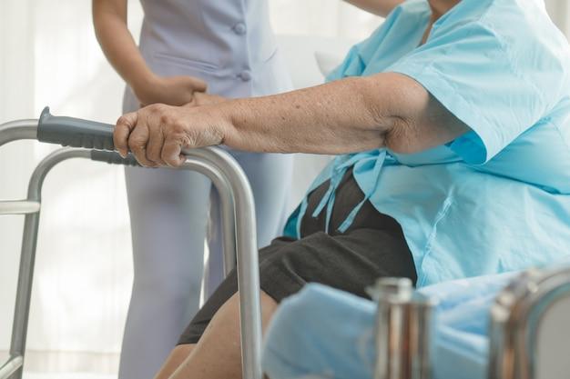 Mantelzorgers helpen ouderen om in de fysiotherapie te lopen.a
