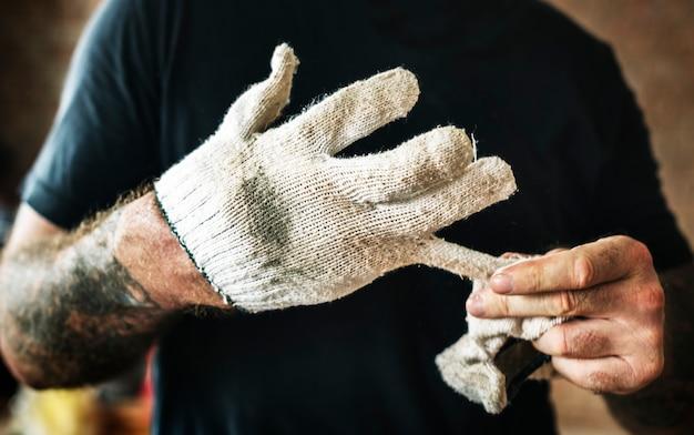 Manusje van alles met tatoegering die een handschoen terugtrekken