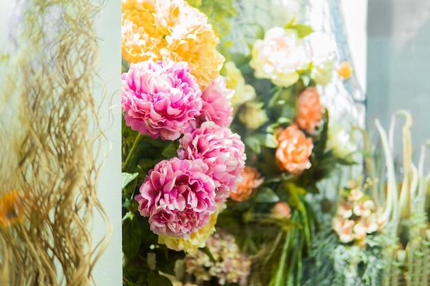 Manydifferent bloemen die bij voorgevel van huis in straat hangen. bloemenwinkel, boeketten op plank, bloemistzaken.