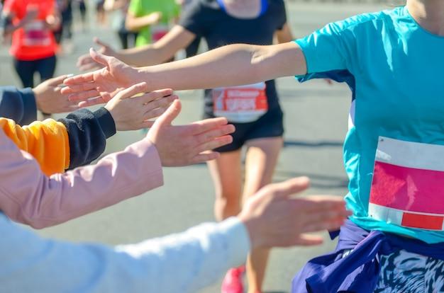 Marathon lopende race, ondersteunende lopers op weg, kinderenhanden die highfive, sportconcept geven