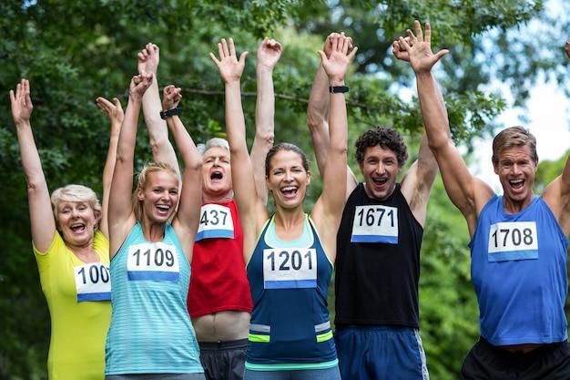 Marathonatleten poseren met opgeheven armen