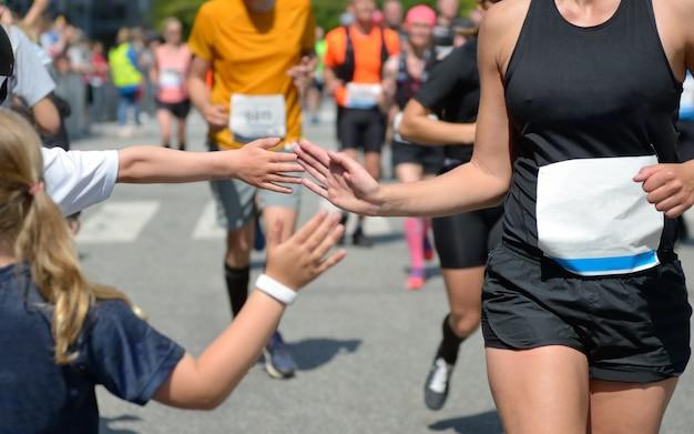 Marathonloopwedstrijd, hardlopersondersteuning op wegwedstrijden, kinderhand geven highfive, kindondersteunende atleten die rennen, sportconcept