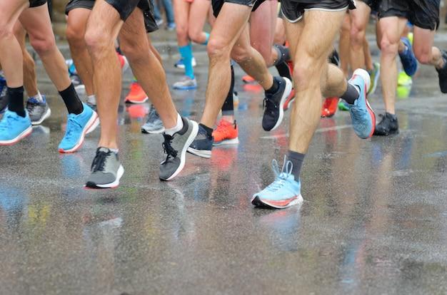 Marathonloopwedstrijd, veel hardlopersvoeten op wegracen, sportcompetitie, fitness en een gezond levensstijlconcept