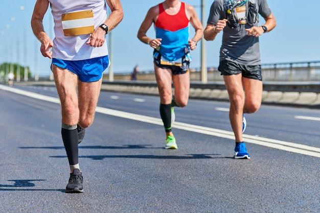 Marathonlopers op stadsweg. loopwedstrijd. straat sprinten buiten